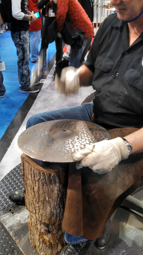 The art of a hand hammering a cymbal